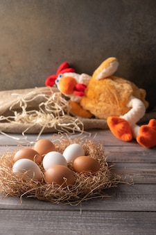 Brown and white chicken eggs in a straw nest on wooden background. next to a chicken toy sleeping. rustic style. copy space