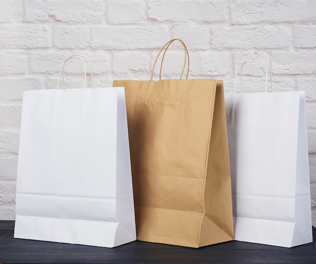 Brown and white paper bags with handles on white brick wall, environmental material, zero waste