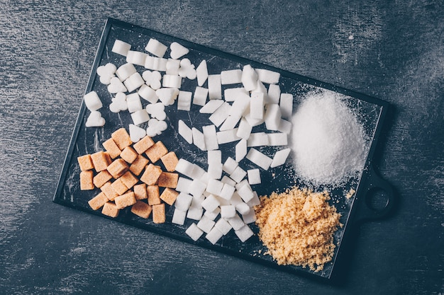 Zucchero bianco e marrone in un tagliere piatto laici