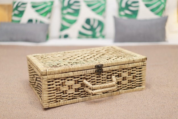 Brown wicker storage basket on bed with many pillow