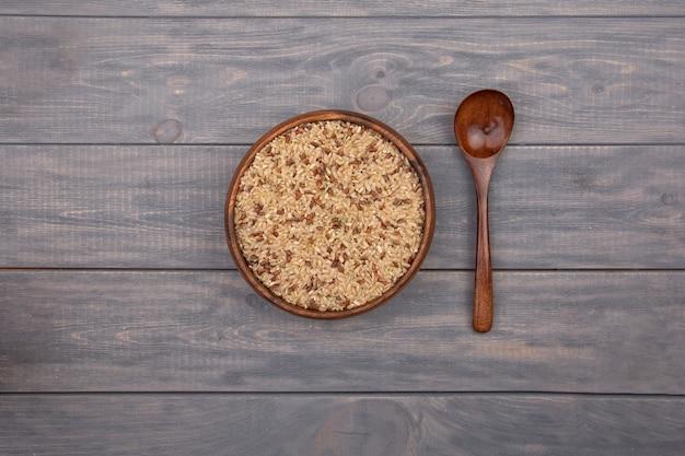 木製のテーブルの上の木の板の玄米。素朴なスタイル。