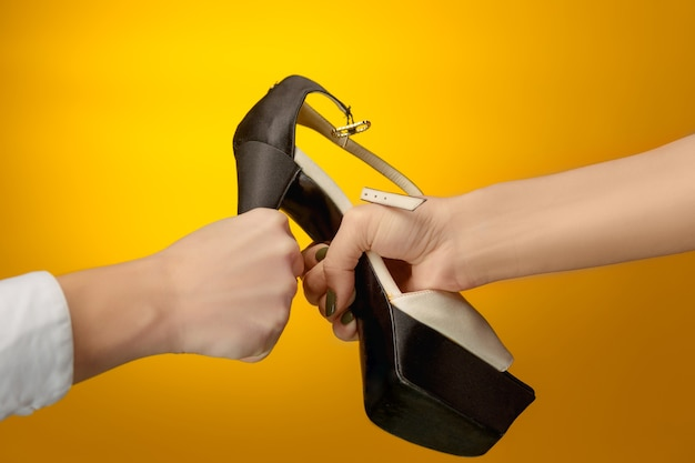 手に女性と男性の茶色の女性の靴