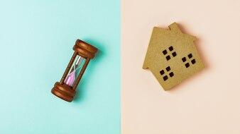 茶色の木の家のアイコンと青とピンクの背景に砂時計
