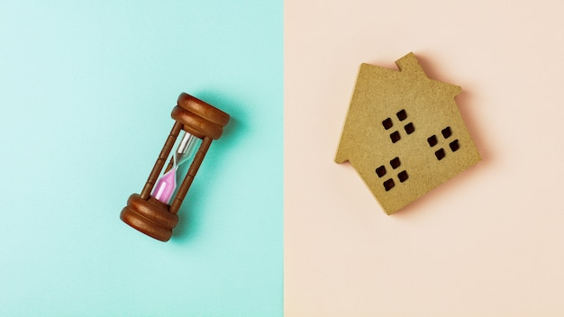 Brown wood home icon and a hourglass on blue and pink background