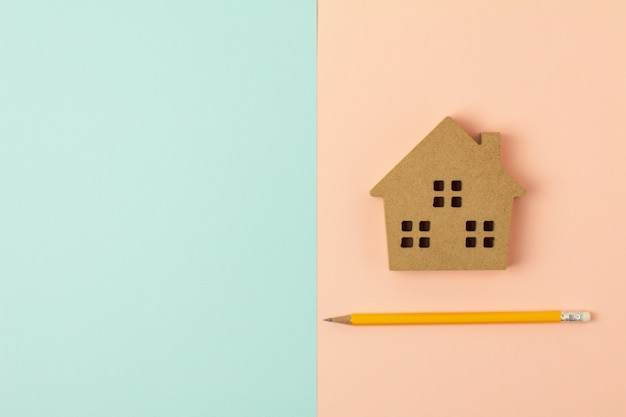 Brown wood home icon and a pencil on blue and pink background