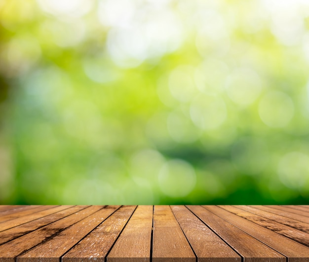 Brown wood surface with a green blurred background