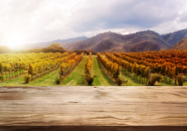Brown wood table in autumn vineyard landscape with empty space for product display