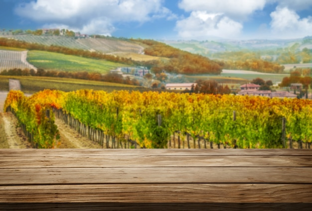 Коричневый деревянный стол в осеннем винограднике с пустым пространством для макета дисплея продукта.