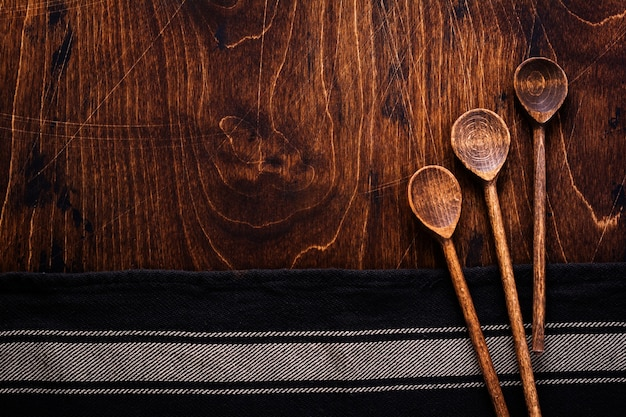 Текстура коричневого дерева с хлопковой кухонной салфеткой или полотенцем и деревянными деревенскими ложками