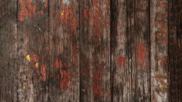 ひびの入ったペイントの背景を持つ茶色の木の質感