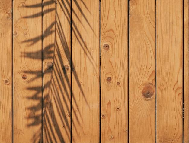 ヤシの葉の影と茶色の木製の背景コピースペースと自然な質感