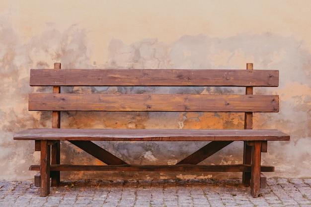 Коричневая деревянная скамейка у старой стены