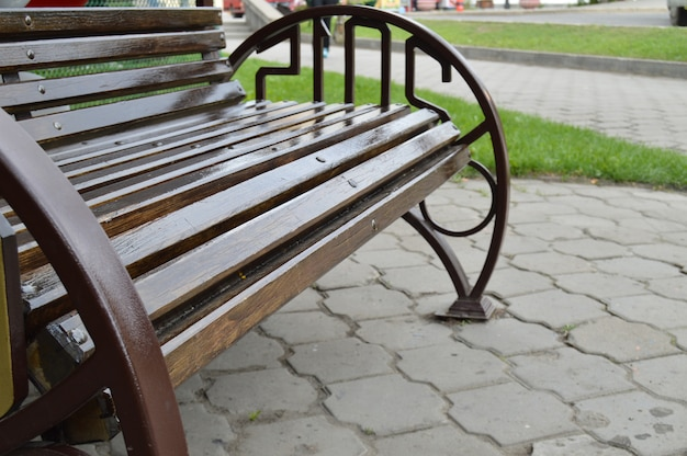 Brown wooden bench on the street in summer park