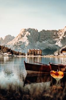 Barca di legno marrone sul lago vicino alla montagna durante il giorno
