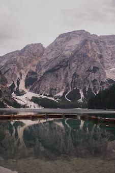 Коричневые деревянные лодки стоят на лазурной воде высокогорного озера лаго ди брайес. доломиты, южный тироль, италия, европа. итальянские альпы.
