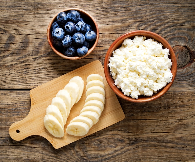 Brown wooden bowl of homemade curd with banana, jam, blueberries