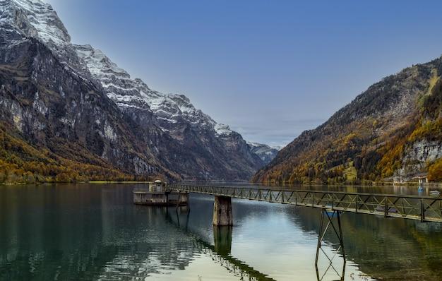昼間の山の近くの湖の茶色の木製ドック