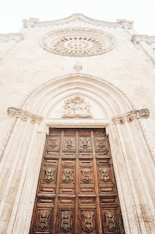 Коричневая деревянная дверь на белом бетонном здании Бесплатные Фотографии