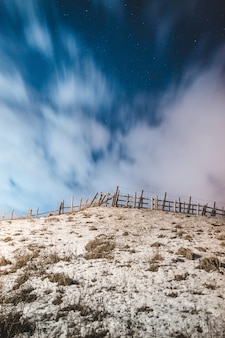 Коричневый деревянный забор на коричневом песке под голубым небом в дневное время