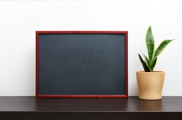 Brown wooden frame or chalkboard mockup in landscape orientation with a cactus in a pot on dark workspace table and white background