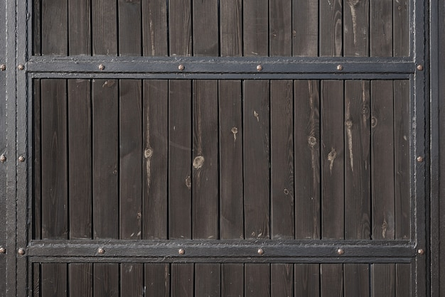 Brown wooden gate with forged metal stripes. backgrounds and textures. close up