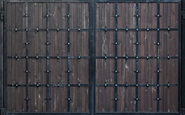 Brown wooden gate with forged metal stripes. backgrounds and textures