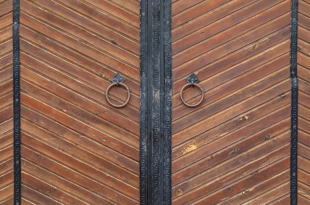 Brown wooden gates with knockers