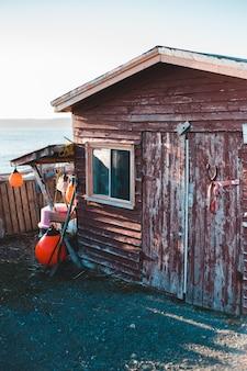 Коричневый деревянный дом возле водоема в дневное время