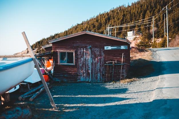Коричневый деревянный дом возле зеленых деревьев в дневное время