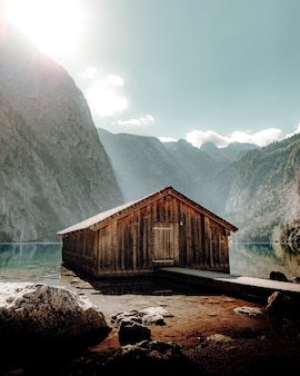 Коричневый деревянный дом возле озера и горы в дневное время
