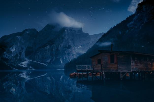 山の近くの湖にある茶色の木造住宅