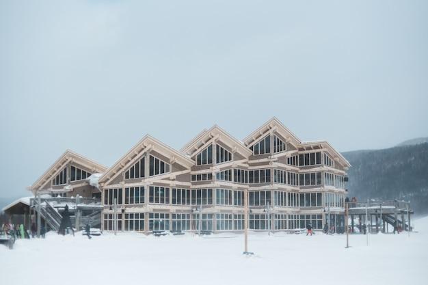 雪の上の茶色の木造住宅は、日中地面をカバー
