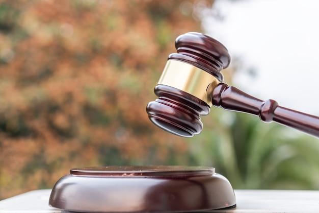 茶色の木製の裁判官は木製のテーブルにガベルを置きます。ビジネスにおける決定のためのオークション入札販売判断マレットまたは弁護士裁判官の概念