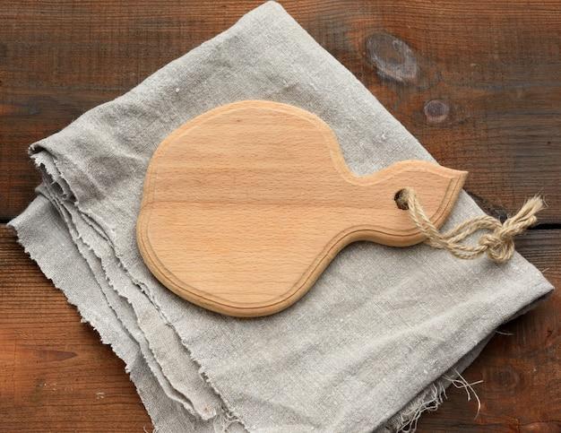 Коричневая деревянная кухонная разделочная доска и серая льняная салфетка на столе, вид сверху