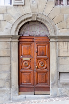 Коричневая деревянная старая дверь в центре бергамо, италии.