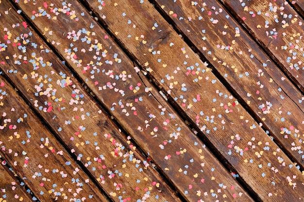 Коричневые деревянные доски, покрытые разноцветным конфетти в форме луны и звезд