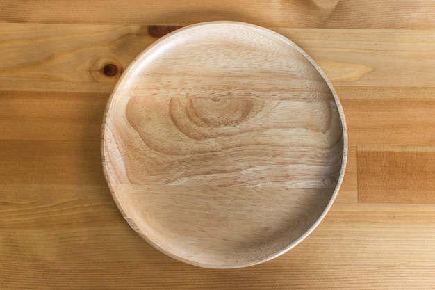 Brown wooden plate on wood table background