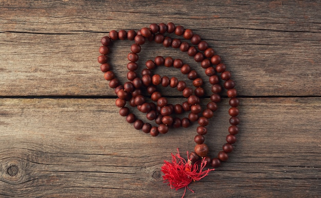 Brown wooden prayer rosary on a wooden background from gray old planks