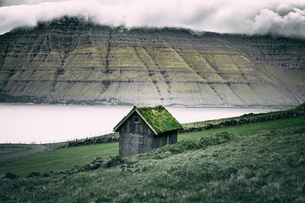 岩の崖の上の屋根に草が付いている茶色の木造の小屋