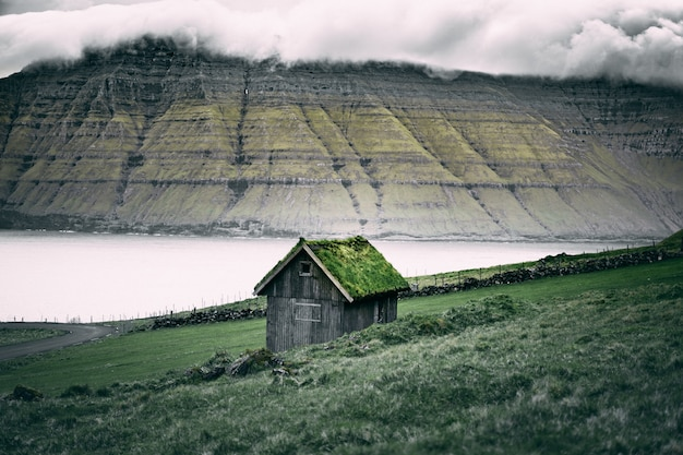 Brown wooden shed with grass on the roof over rock cliffs