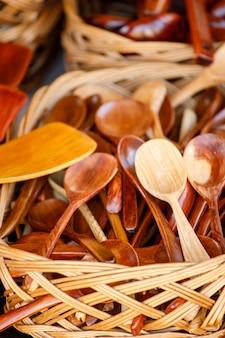 Brown wooden spoons lie in a basket.