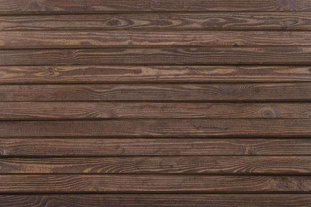 Коричневый деревянный стол из сосновых досок. темный фон с грубой текстурой поверхности.