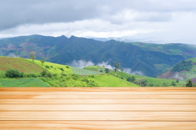 Brown wooden table on green mountain view