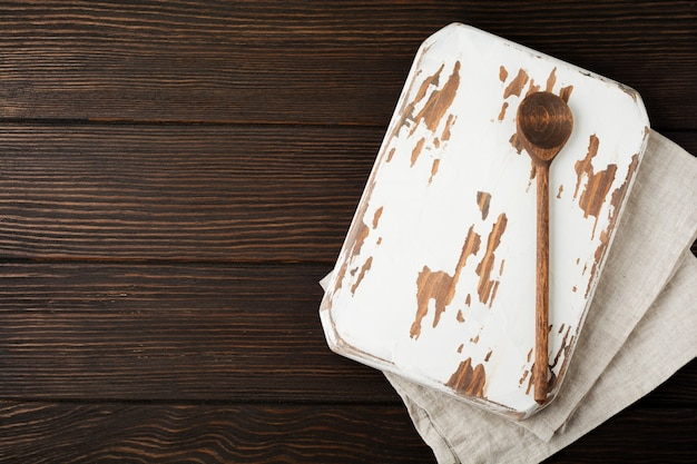 Brown wooden texture with old chopping board and wooden spoon. background. top view.