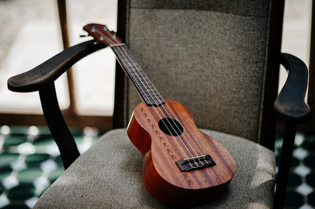 Brown wooden ukulele resting on a wooden chair