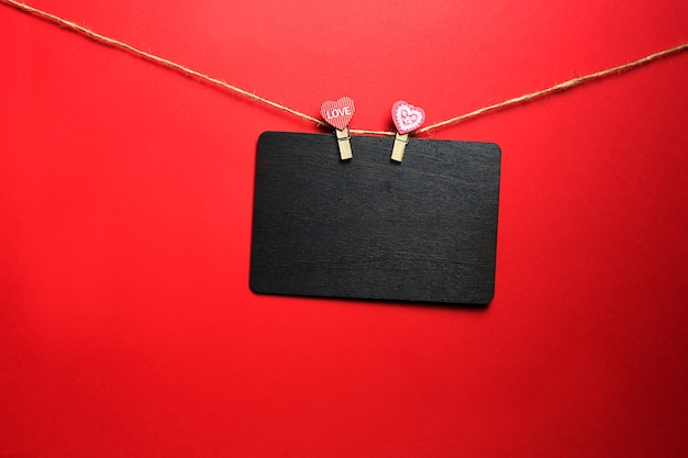 A brown wooden writing board with copyspace hangs on a rope with two clothespins with hearts and the inscription love. valentine's day, mock up for lovers. red background, frame