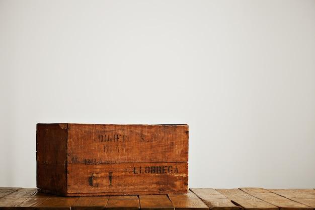 Коричневая изношенная деревенская коробка с черными буквами на деревянном столе в студии с белыми стенами
