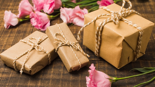 Brown wrapped gift boxes and pink eustoma flowers on wooden surface