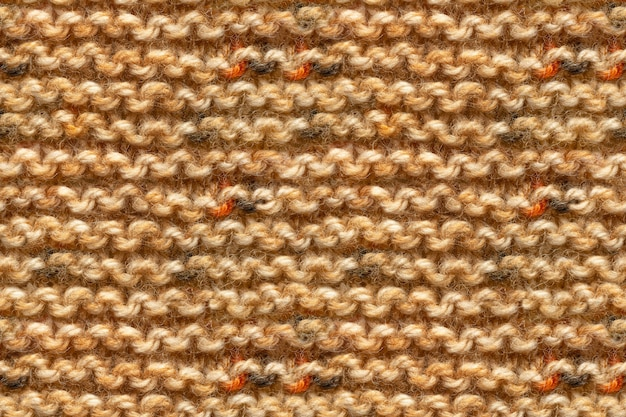 Brown yellow beige color knitwear fabric texture. knitting texture macro snapshot. beige knitted