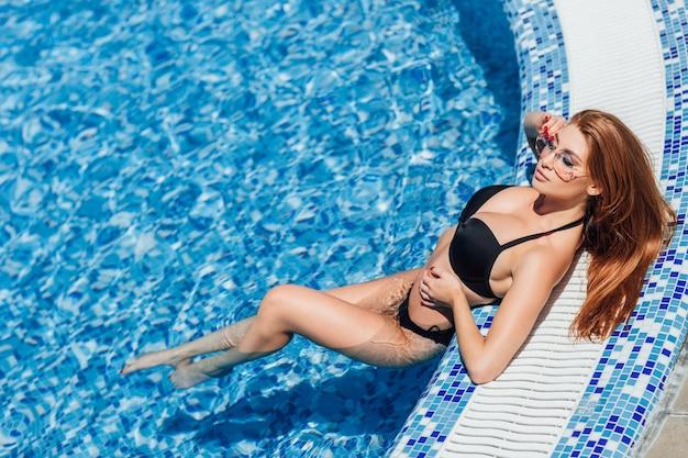 プールで横になって日光浴をしている姿と巨乳の茶色の髪の女性
